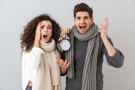 Image of upset couple man and woman screaming while holding alarm clock isolated over gray background