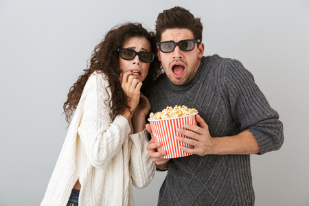Image of excited man and woman wearing 3d goggles holding bucket with pop corn isolated over gray background