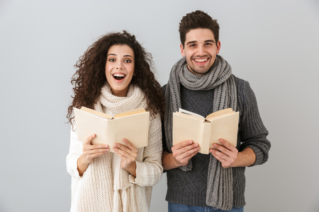 Image of excited man and woman reading books together isolated over gray background Stock Photo - 114932734