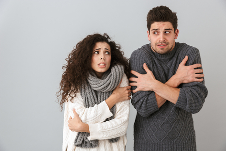 Photo of displeased couple man and woman wearing scarfs trembling and hugging themselves isolated over gray background
