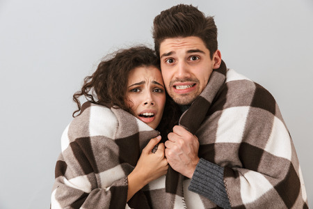 Photo of frozen couple man and woman wrapped in blanket trembling and hugging together isolated over gray background 스톡 콘텐츠
