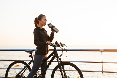 Photo of caucasian woman drinking water while riding bicycle on boardwalk during sunrise over sea Stock Photo