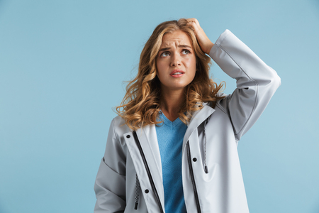 Confused young girl wearing raincoat standing isolated over blue background