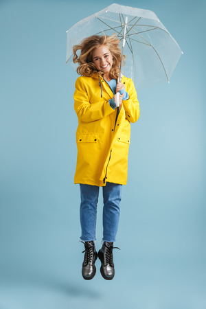 Full length image of positive woman 20s wearing yellow raincoat standing under transparent umbrella isolated over blue background Stock Photo