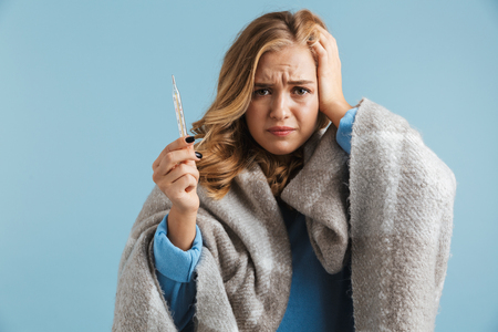 Image of sick young woman 20s wrapped in blanket holding thermometer isolated over blue background