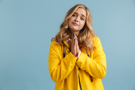 Image of blonde woman 20s wearing yellow raincoat keeping palms together for pray isolated over blue background Stock Photo