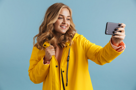 Image of content woman 20s wearing yellow raincoat holding cell phone and taking selfie photo isolated over blue background Stock Photo