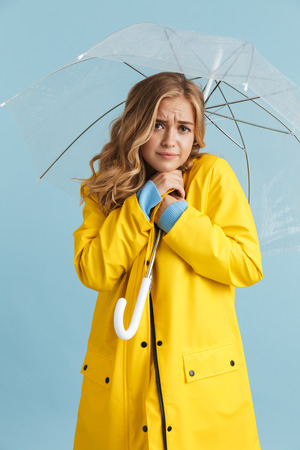 Full length image of elegant woman 20s wearing yellow raincoat standing under transparent umbrella isolated over blue background