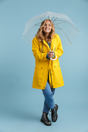 Full length image of european woman 20s wearing yellow raincoat standing under transparent umbrella isolated over blue background Stock Photo