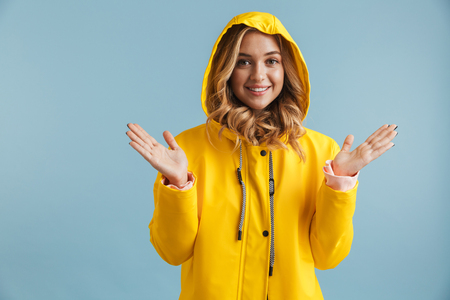 Image of joyful woman 20s wearing yellow raincoat looking at camera isolated over blue background