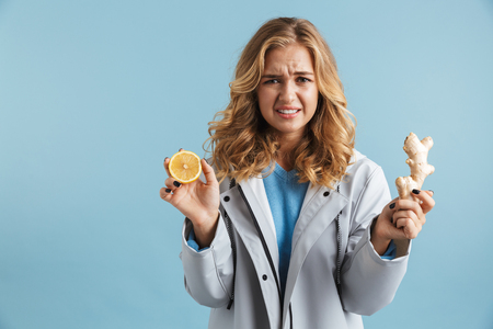 Confused young girl wearing raincoat standing isolated over blue background, showing lemon and ginger