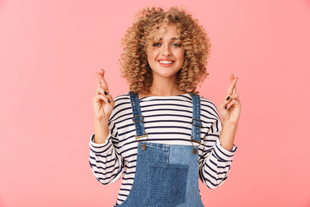 Cheerful young woman with curly hair wearing casual clothes standing isolated over pink background, holding fingers crossed for good luck
