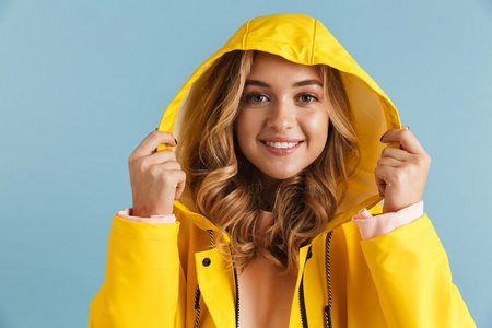 Image of cheerful woman 20s wearing yellow raincoat smiling at camera isolated over blue background