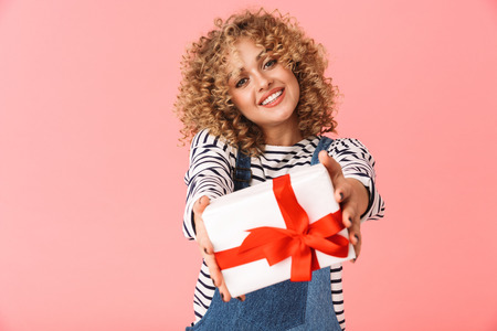Photo of lovely curly woman 20s holding gift box while standing isolated over pink background