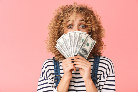 Photo of successful curly woman 20s holding fan of dollar money while standing isolated over pink background