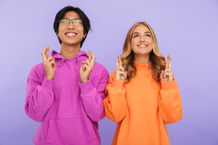Cheerful multhiethnic teenage couple standing together isolated over violet background