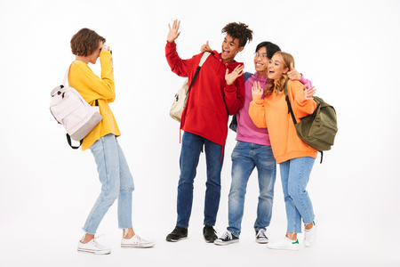 Group of cheerful teenagers isolated over white background, carrying backpacks, taking a picture