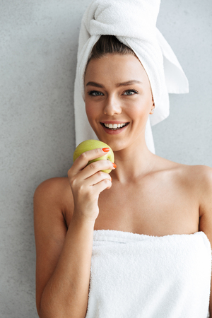Beautiful young woman wrapped in a bath towel standing at the wall at home, holding green apple