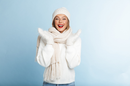 Lovely young woman wearing sweater and hat isolated over blue background Banque d'images