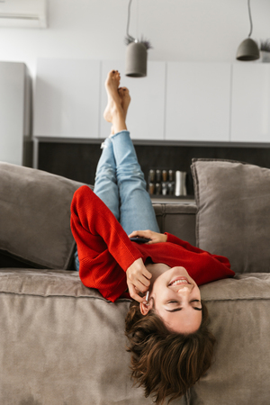 Cheerful young woman relaxing at home, listening to music with wireless earphones, holding mobil phone