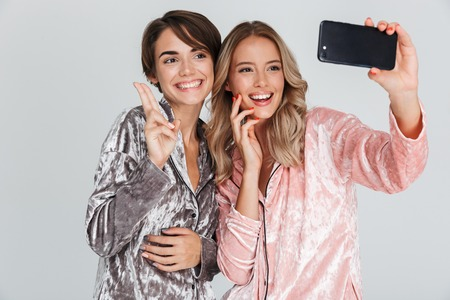 Two pretty girls wearing pajamas isolated over gray background, taking a selfie