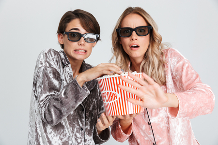 Two excited girls wearing pajamas standing isolated over gray background, watching a movie, eating popcorn 스톡 콘텐츠