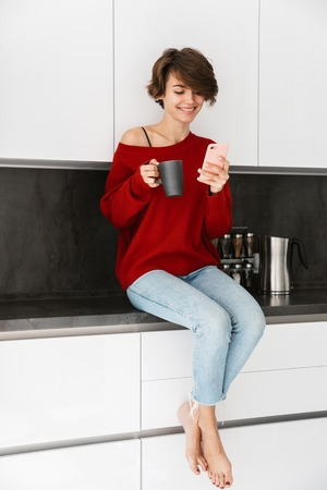 Smiling younh woman wearing sweater sitting on a kitchen table at home, using mobile phone, drinking coffee Stockfoto
