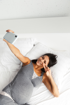 Image of an amazing healthy pregnant woman indoors at home lies in bed take a selfie by phone. 写真素材