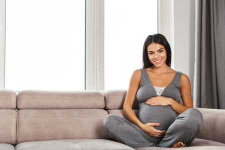 Image of an amazing healthy pregnant woman indoors at home sitting posing on sofa.