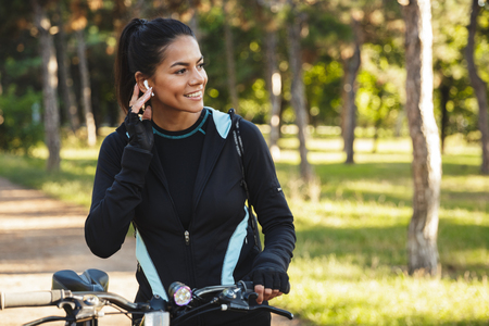 Attractive fit sportswoman with a bicycle at the park, listening to music with wireless earphones