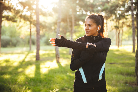 Beautiful fit sportswoman doing warming up exercises before jogging at the park, listening to music with earphones Stock fotó