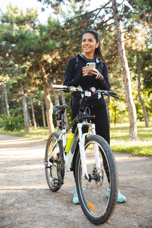 Attractive fit sportswoman with a bicycle at the park, listening to music with wireless earphones, using mobile phone Reklamní fotografie - 115702776