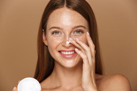Image de beauté d'une jolie femme torse nu souriante et tenant un pot avec de la crème pour le visage isolée sur fond beige
