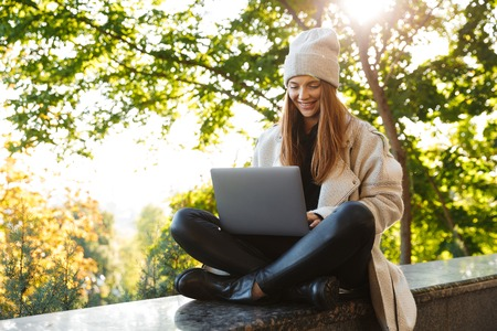 Beautiful young woman dressed in autumn coat and hat sitting outdoors, using laptop computer 写真素材