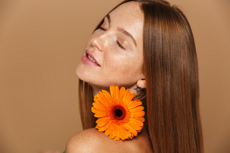 Beauty image of young shirtless woman 20s standing with orange flower isolated over beige background Stock Photo - 115701810