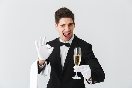 Portrait of a smiling young waiter in tuxedo offers you a glass of champagne over white background Foto de archivo - 117380092