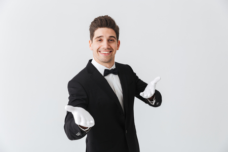 Portrait of a handsome young man waiter wearing tuxedo and gloves standing isolated over white background Foto de archivo