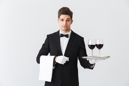 Handsome young waiter wearing tuxedo presenting a tray with two glasses of red wine isolated over gray background
