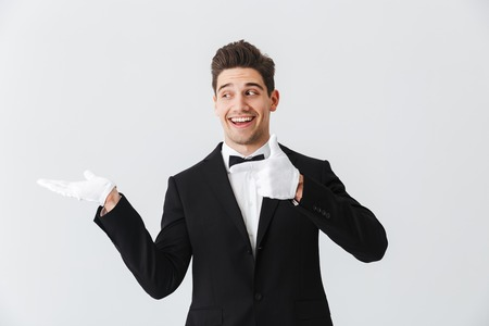 Portrait of a handsome young man waiter wearing tuxedo and gloves standing isolated over white background, presenting copy space Stok Fotoğraf
