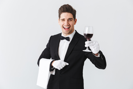 Handsome young waiter wearing tuxedo holding glass of red wine isolated over gray background