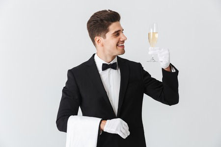Portrait of a smiling young waiter in tuxedo offers you a glass of champagne over white background Foto de archivo - 117380612