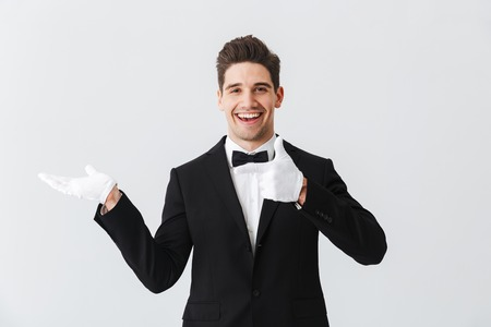 Portrait of a handsome young man waiter wearing tuxedo and gloves standing isolated over white background, presenting copy space Stock Photo
