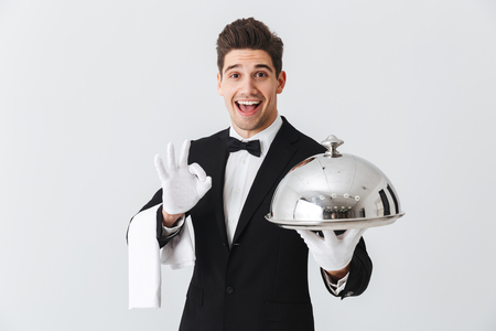 Happy young waiter in tuxedo holding serving tray with metal cloche and napkin, showing ok