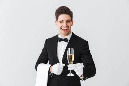 Portrait of a smiling young waiter in tuxedo offers you a glass of champagne over white background Foto de archivo - 115886043