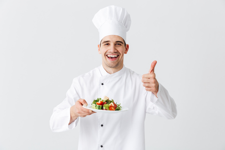 Excited man chef cook wearing uniform showing fresh green salad on a plate isolated over white background, thumbs up
