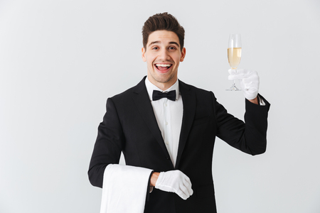 Portrait of a smiling young waiter in tuxedo offers you a glass of champagne over white background Foto de archivo - 115886274