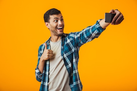 Cheerful young man wearing plaid shirt standing isolated over orange background, taking a selfie Stock Photo