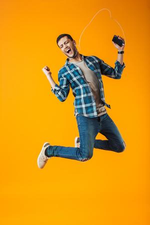 Aufgeregter junger Mann mit kariertem Hemd, der isoliert über orangefarbenem Hintergrund springt und Musik mit Kopfhörern und Mobiltelefon hört
