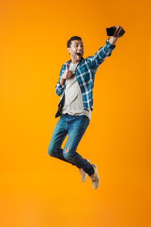 Full length portrait of a happy young man wearing plaid shirt isolated over orange background, jumping, taking a selfie