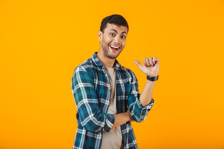 Cheerful young man wearing plaid shirt standing isolated over orange background, pointing finger at himself